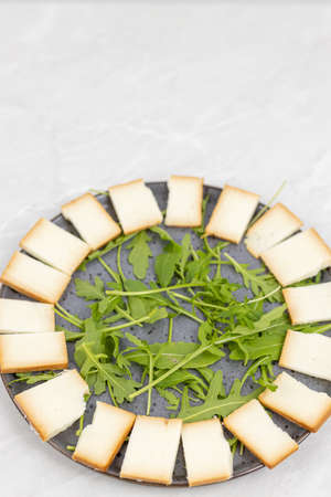 Sliced smoked cheese with rucola on the plate.