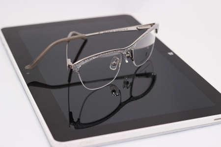 diopter: gafas con dioptr�as, y la tableta en el fondo blanco Foto de archivo