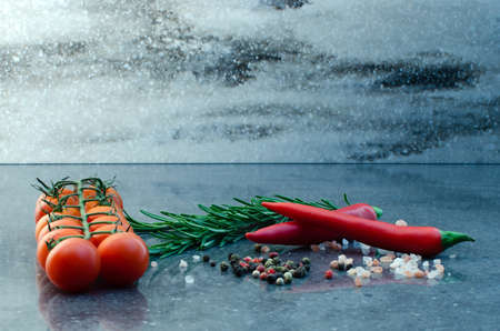 Dark food background with empty board, cherry tomatoes, rosemary, coarse himalayan salt and pepper. Free space for text or product. Copy space