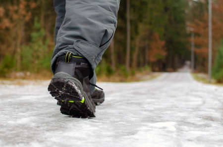 A man walks on a slippery road, the first snow in the park, winter shoes, the road is covered with slippery ice.