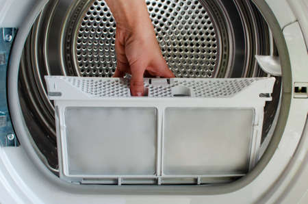 A housewife holds a lint trap from a front-loading tumble dryer. Womans hand