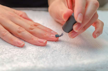 A woman applies a primer to her nails before applying varnish. Close-up of a hand.