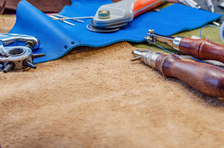 Leather craft tools on leather background, place for text, copy space. Leather shoemaker concept.