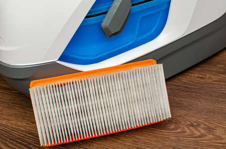 Vacuum cleaner filter with water filter. Large white vacuum cleaner on a brown floor.