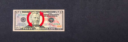 Dollar inflation, dollar depreciation, decline in the purchasing power of the American currency. Copy space. Fifty dollar banknote on black background and up arrow.
