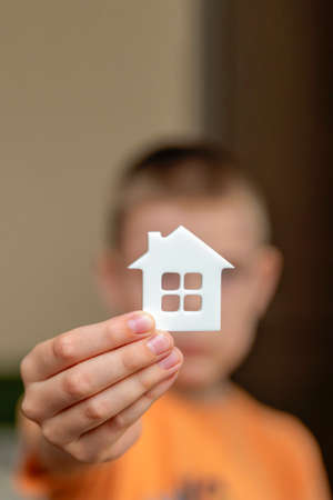 Orphanage, children in the orphanage. The child is holding a small house-shaped figurine, close-up. Adoption concept. Banner, place for text