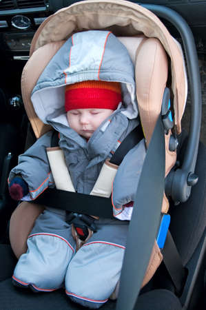 The child sleep in a safety seat on forward sitting of the car. photo