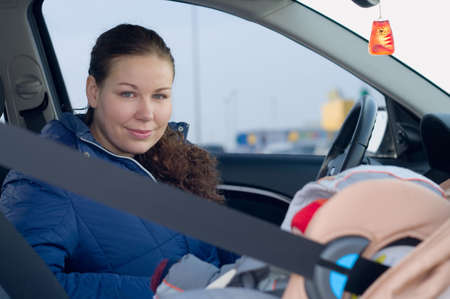 The child in a safety seat near to mother who sits on forward sitting of the car. photo