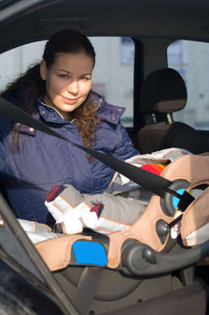 Mother fastens a childrens safety seat with the child in the car on a back seat. photo
