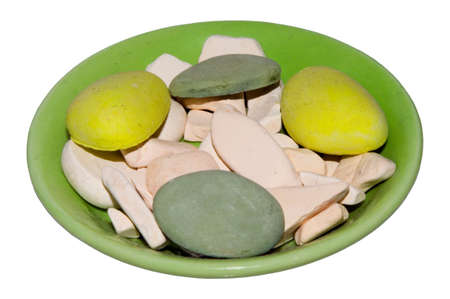 smoothfaced: Green plate with round color pebbles. Theirs colors are yellow, grey and white.