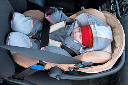 The child sleep in a safety seat on forward sitting of the car.