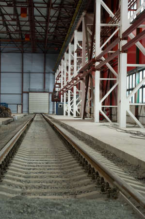 distant work: Railroad going into the distance in hangar near from hardware. Metal columns and ceiling. Stock Photo