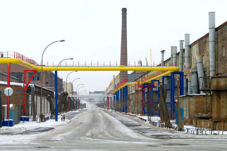 New yellow pipeline with blue and red hardware across the road on the old factory Stock Photo - 4679933