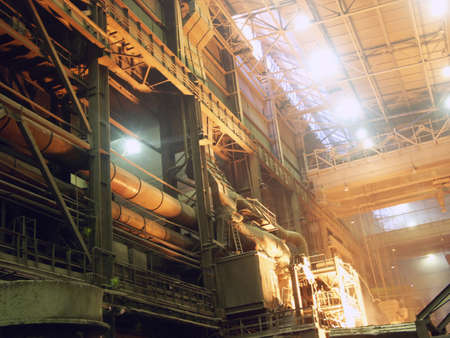 ferrous foundry: Casthouse in ferrous metallurgy factory with large-tonnage crane under roof and pipes along a wall.