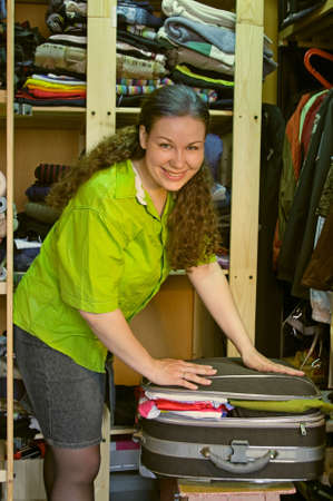 Woman in the wardrobe packs things into a suitcase and smiles photo