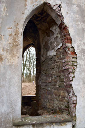 Window opening in brick ancient wall. Old castle ruins. Woman in the window going away. photo
