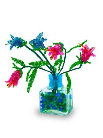Handmade article: vase with flowers from glass beads and wire. Red, blue bud. Green foliage. Transparent bowl. photo