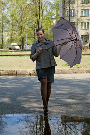 Young woman stays before puddle with grey umbrella. Sunny day in the city Stock Photo - 4923744