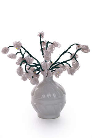 Handmade article: vase with flowers from glass beads and wire. White bowl. photo