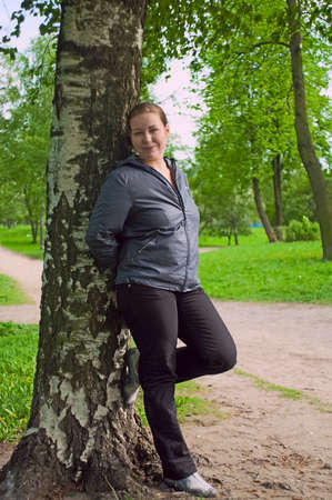 Young woman stands near the birch in forest. Green foliage around photo