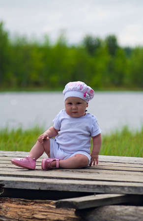 sitting area: Little Child is sitting on the timber flooring near lake. It is summer. Infant is one years old. It`s a girl.