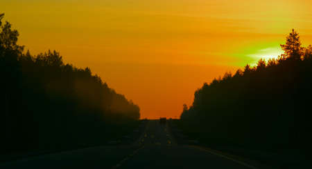 Sunset on the road. Lonely car moving along to horizon. Orange sky in yellow sun lights and dark roadside. Stock Photo - 5082117