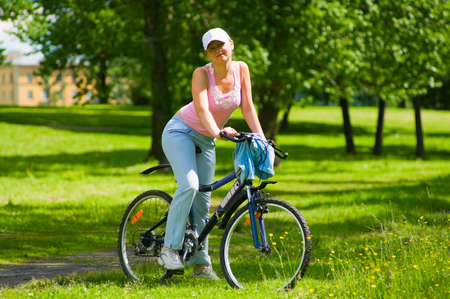 Young woman biker on the bicycle stand in the park. She stops to ride on bicycle. It`s a hot summer. Stock Photo - 5111297