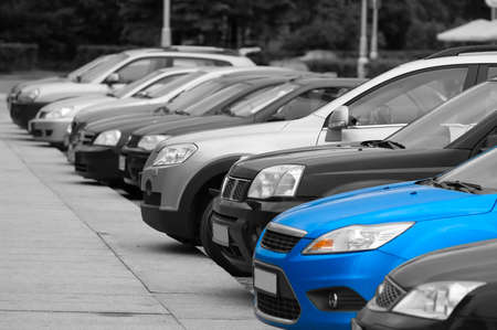 car garage: Black-and-white cars are on the parking and only one blue colored automobile.