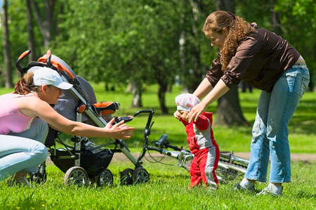 Two women help toddler to do first steps in the park. Green grass and foliage around they. It`s a summer. Baby carriage and bike are here too. photo