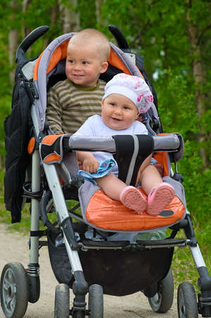 Two children in baby carriage. There is one years difference of age between them. They are brother and sister photo