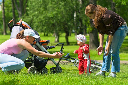 Two women help toddler to do first steps in the park. Green grass and foliage around they. It`s a summer. carriage and bike are here too. photo