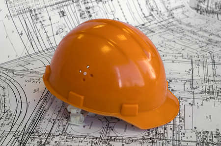 Orange constructional helmet and project drawings. Business objects on the construction dimensioned drawing photo