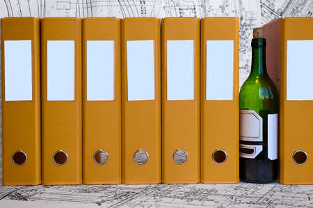 deadlock: Bottle of wine between yellow data folders. Hard drinking on the jobsite