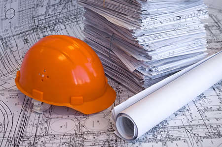 Orange helmet and heap of project drawings photo
