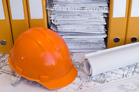 Yellow, red file folders, helmet and heap of design drawings are on the table. Business still-life. photo