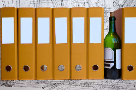 debauchery: Bottle of wine between yellow data folders. Hard drinking on the jobsite