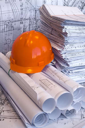 designing: Orange helmet and heap of project drawings Stock Photo