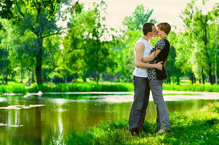 lovers kissing: Teenagers: man are kissing girlfriend on nature near a lake. Full-length portrait Stock Photo