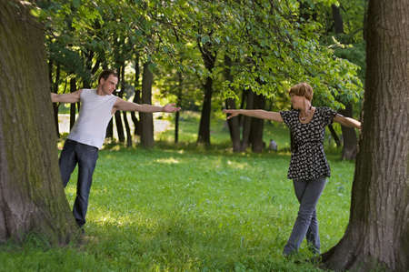 Teenagers: man and woman are stretching one's hand for each other. It is on nature. Full-length portrait Stock Photo - 5254174