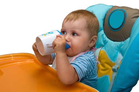 Cute toddler drinks juice in chidren seat
