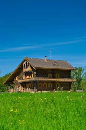 Wooden big house from timbers and windows on it. It is in a village in Russia. Sunny day photo