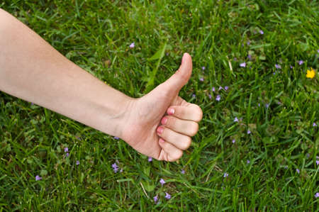 Thumb up in green meadow background. Caucasian woman`s hand photo
