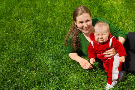 Young mother and her little baby are on green grass. They are smiling. There is free area near them from grass. Green background. Red clothes on the baby. Summer. photo
