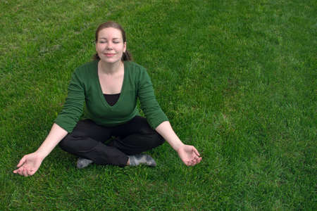 Young woman sitting on green grass in pose of meditation Stock Photo - 5406051