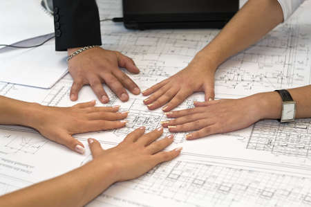 clasped hand: Human hands on table with a project drawings. Stock Photo