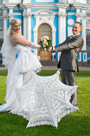 Loving newly-married couple on green grass and white umbrella near  photo