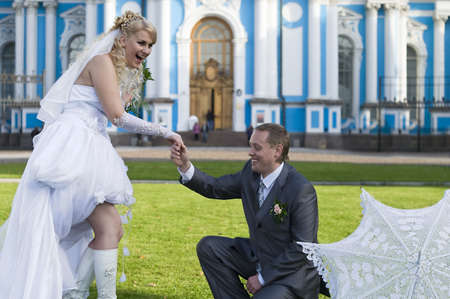 Young groom proposes marriage to bride near a church photo