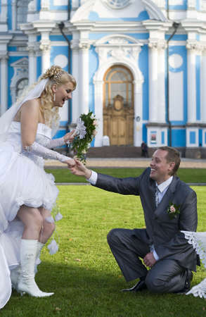 Loving young wedding couple are on grass near a church Stock Photo - 6106624