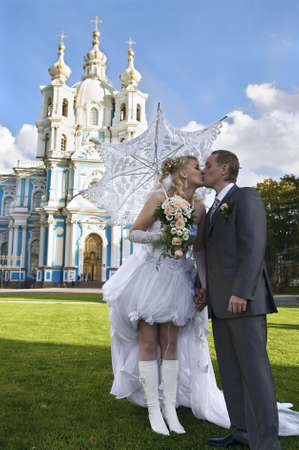 Loving newly-married couple kissing. Staying on green grass  photo