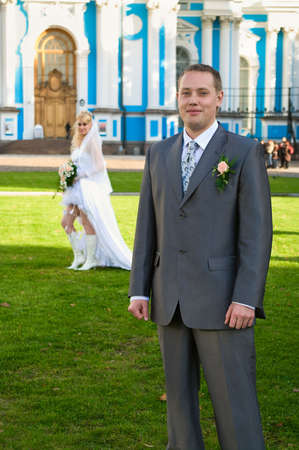Groom on foreground and bride om background. Sunny summer day photo